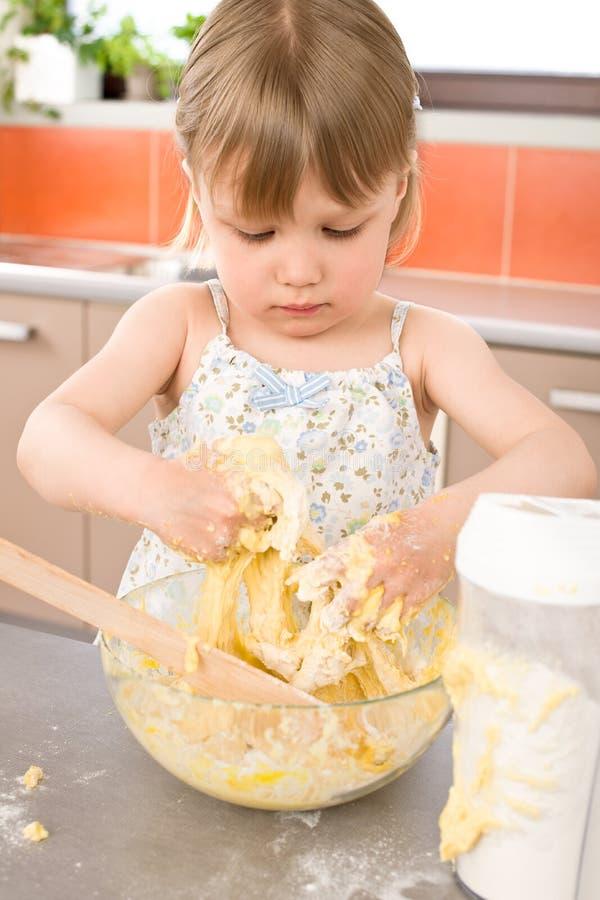 烘烤儿童揉一点的面团女孩 免版税库存照片