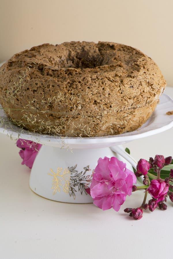 烘烤圆环蛋糕用糖粉,与桃红色花 免版税图库摄影