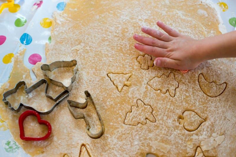 烘烤圣诞节曲奇饼的孩子切酥皮点心 免版税库存照片