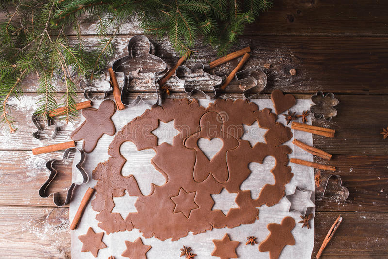 烘烤圣诞节曲奇饼重点月亮塑造星形 铺开面团删去星和gingerbreadman在木背景 库存照片