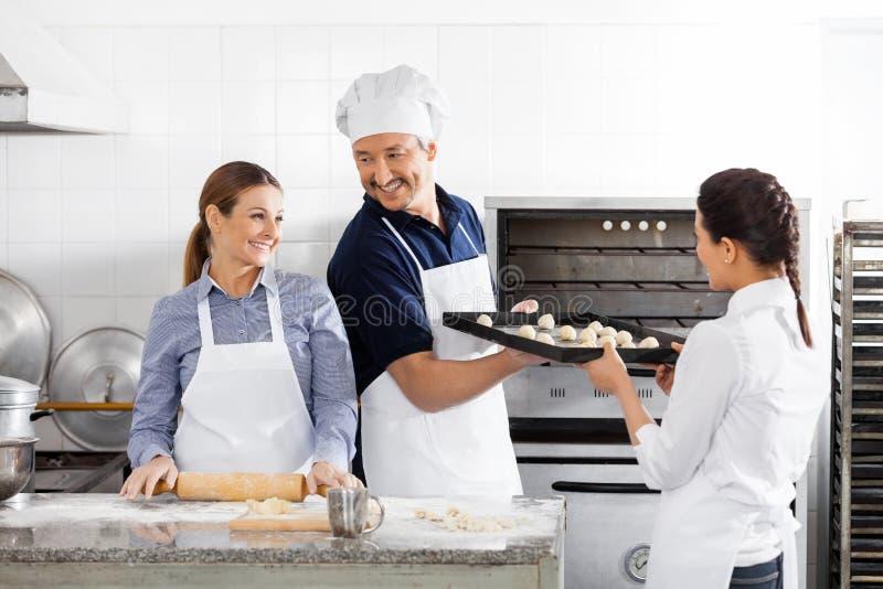 烘烤在厨房里的愉快的厨师 免版税库存照片