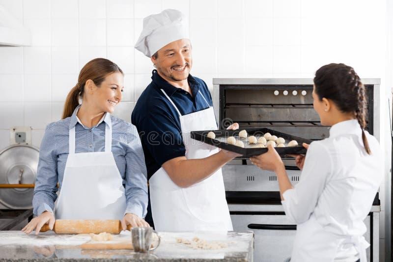烘烤在商业厨房的愉快的厨师 图库摄影