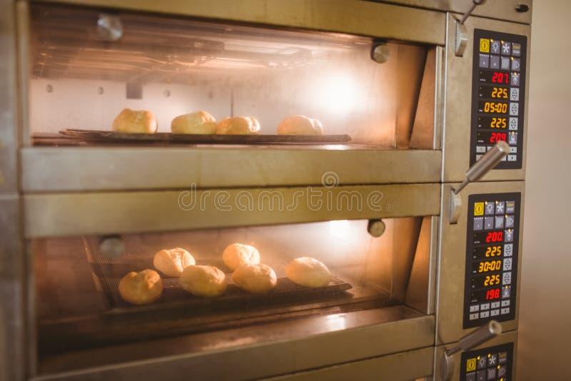 烘烤在烤箱的小圆面包 库存照片