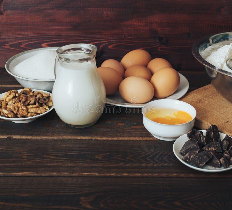 烘烤成份:牛奶,糖,鸡蛋,巧克力,在土气木头的核桃 免版税库存照片