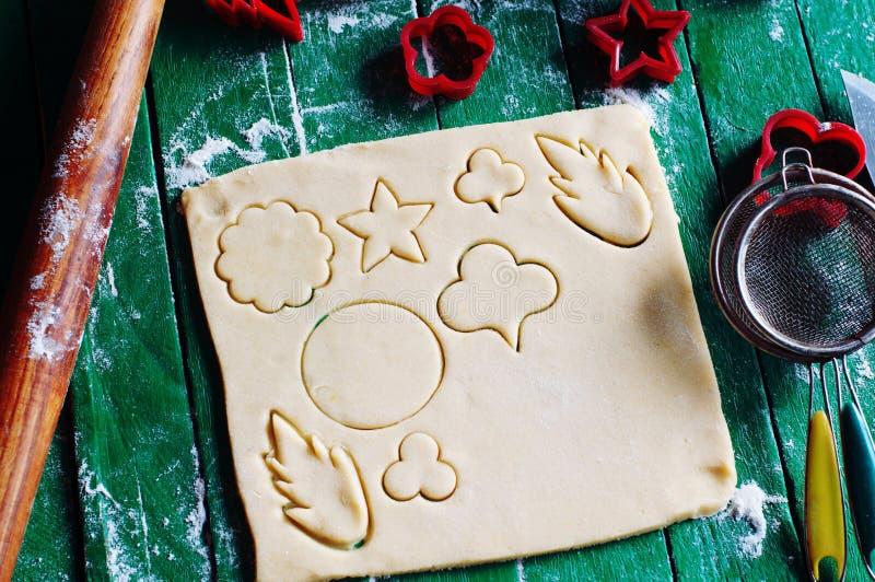 烘烤曲奇饼的过程在家 新鲜的面团准备好烘烤在土气绿色木背景 面团成份和decoratio 免版税库存照片