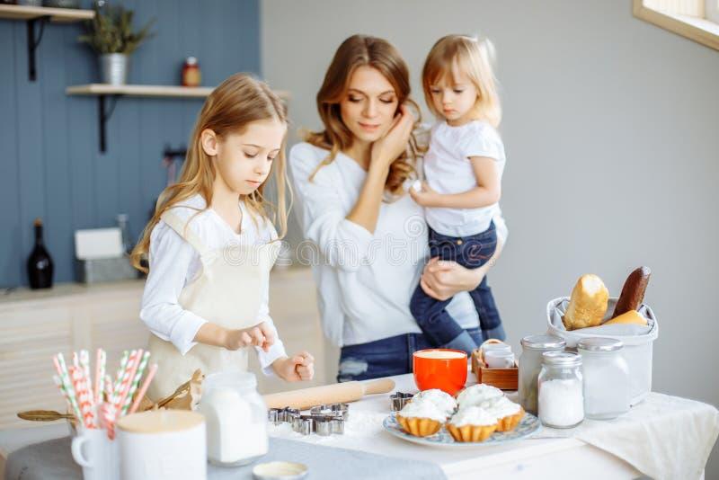 烘烤杯形蛋糕的母亲和两个逗人喜爱的小女孩的画象在厨房里 库存图片