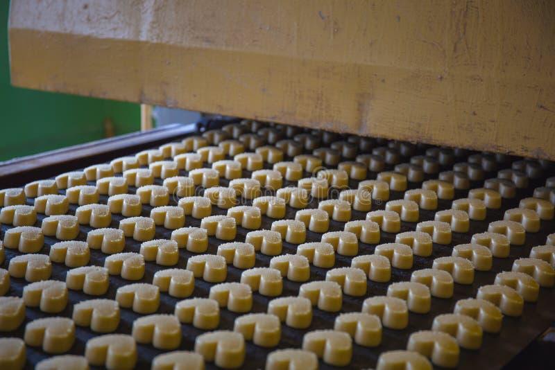 烘烤生产线在曲奇饼工厂 未煮过的饼干以心脏的形式在传送带的 免版税库存照片