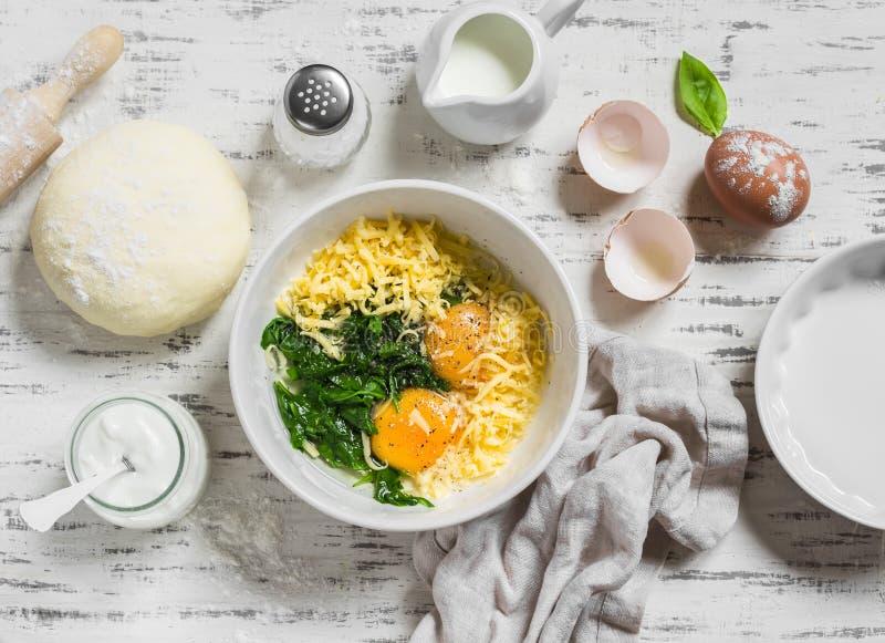 烘烤的一个饼未加工的成份用菠菜-鸡蛋,乳酪,面团,菠菜,在轻的木背景的奶油 免版税库存图片