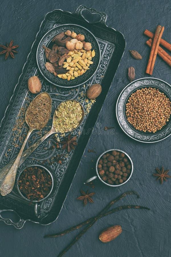 烘烤的姜饼、松饼或者加香料的热葡萄酒的-香草,桂香,香菜,丁香豆蔻果实在灰色的茴香肉豆蔻香料 免版税库存图片