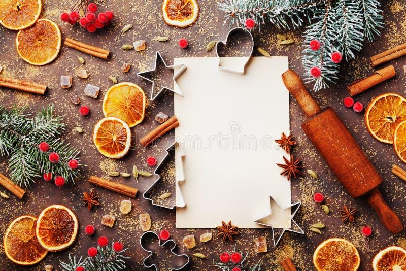 烘烤的姜饼曲奇饼的食物背景与切削刀、滚针和香料在台式视图 圣诞节食谱 免版税库存图片