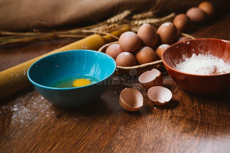 烘烤的蛋糕在农村厨房-面团食谱成份鸡蛋,面粉,在葡萄酒木桌上的糖里从上面 免版税库存照片