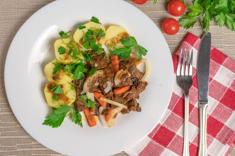烘烤肉用土豆和红萝卜 库存图片