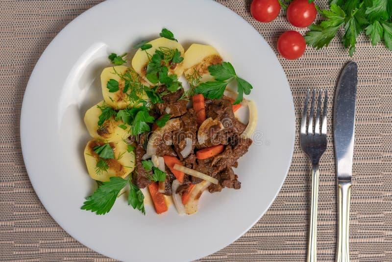 烘烤肉用土豆和红萝卜 库存照片
