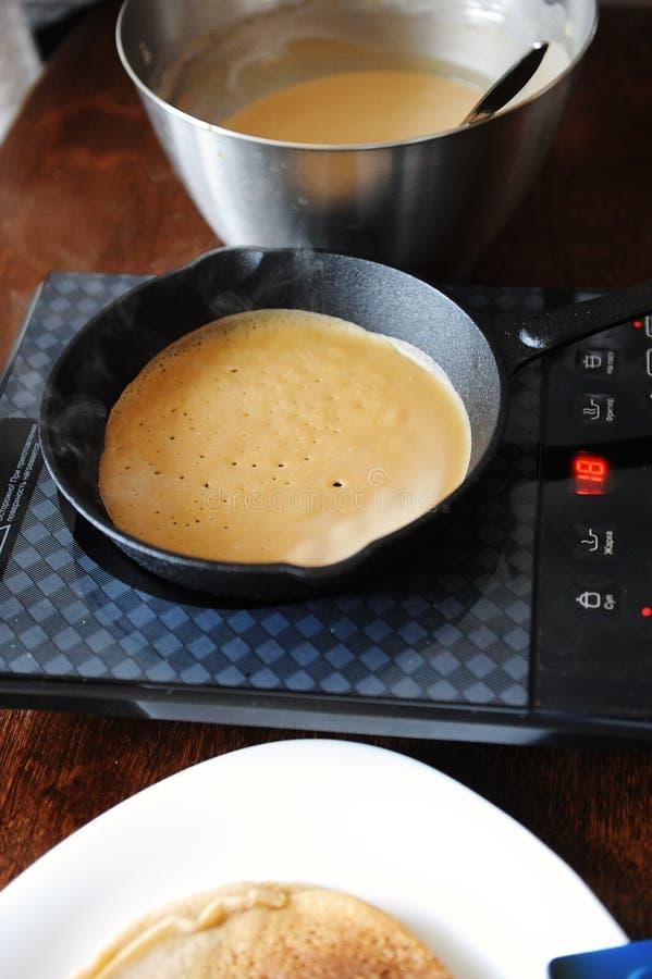 烘烤薄煎饼的过程 在生铁长柄浅锅的精美多孔绉纱 在电感应烹饪器材火炉 热蒸汽 免版税库存图片