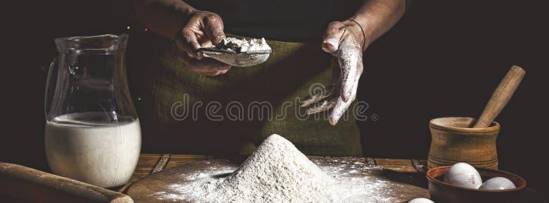 烘烤 供以人员准备面包、复活节蛋糕、复活节面包或者跨小圆面包在木桌上在面包店关闭  准备面包窦的人 免版税库存照片