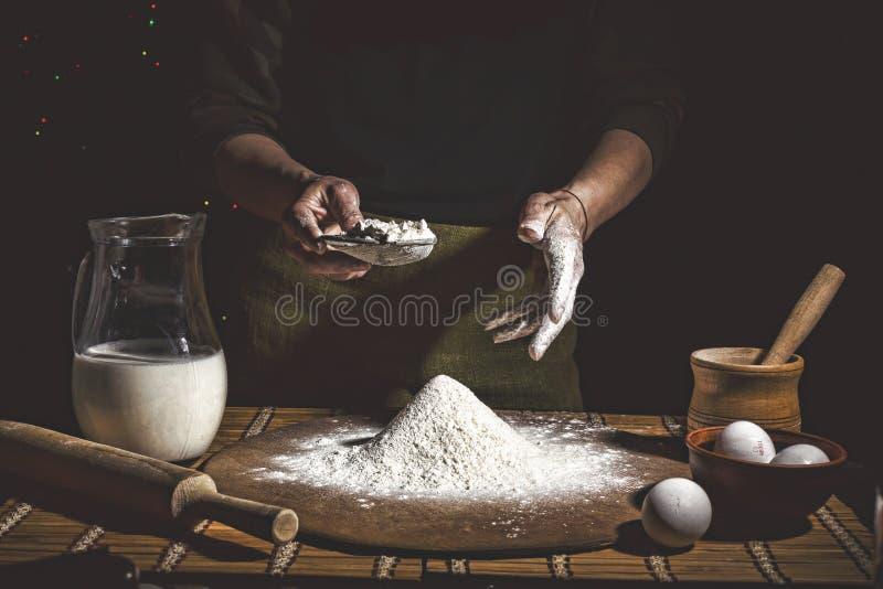 烘烤 供以人员准备面包、复活节蛋糕、复活节面包或者跨小圆面包在木桌上在面包店关闭  准备面包窦的人 免版税图库摄影
