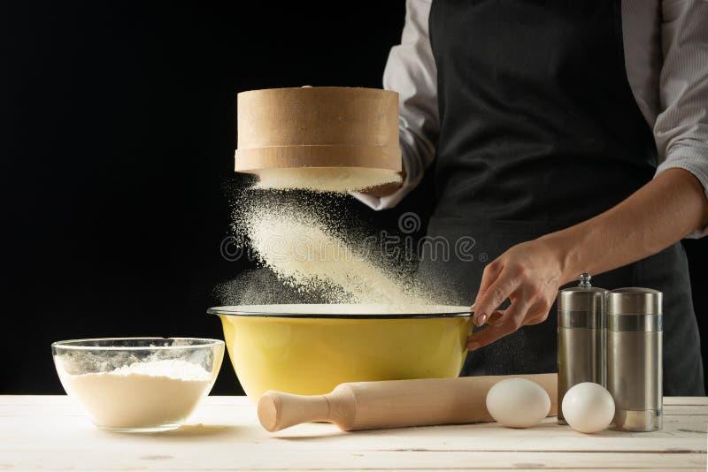 烘烤 供以人员准备面包、复活节蛋糕、复活节面包或者跨小圆面包在木桌上在面包店关闭  准备面包窦的人 库存照片