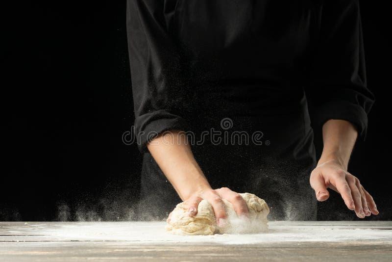 烘烤 准备面包、复活节蛋糕、复活节面包或者有十字架形的圆形圣糕在一张木桌上的人在面包店关闭  烹调准备 免版税图库摄影