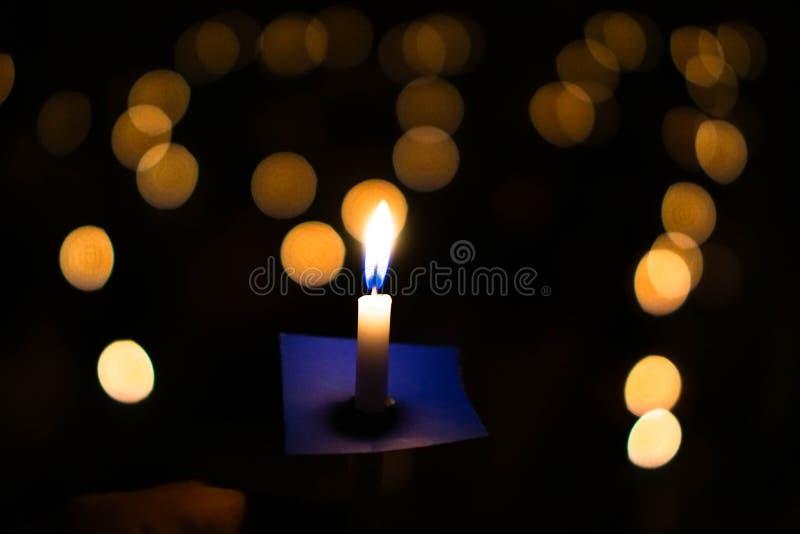 烛光焰在与bokeh的晚上在黑暗的背景与去ligh 免版税库存照片