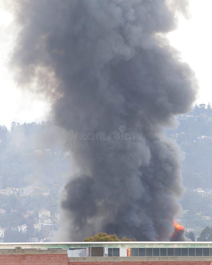 烟和火焰从仓库火在奥克兰加州 免版税库存照片