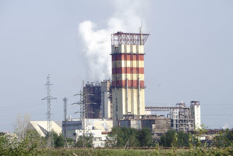 烟斗反对蓝天的热电厂 免版税图库摄影