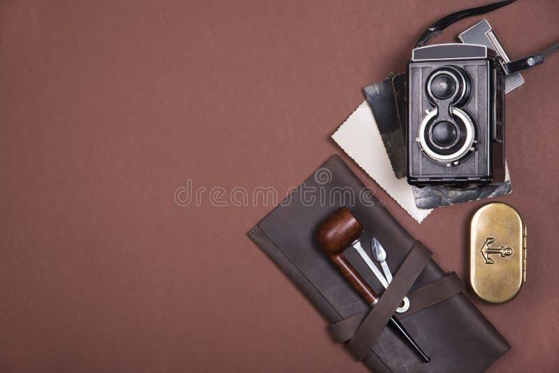 烟斗的构成在一张棕色皮革盒、烟草辅助部件、老照相机和葡萄酒照片的 顶视图 免版税库存图片
