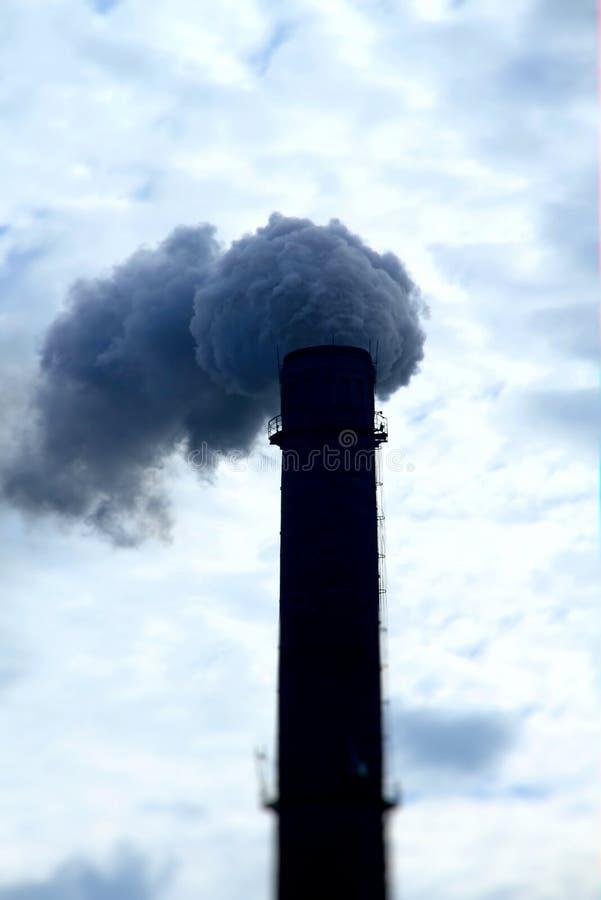 从烟窗的毒性烟污染在多云天空 免版税库存图片
