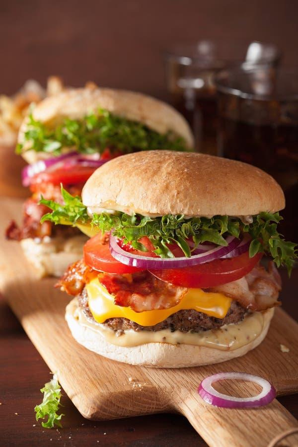 烟肉乳酪汉堡用牛肉小馅饼、蕃茄和葱 免版税库存照片