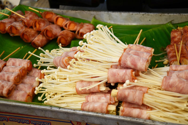 烟肉包裹了Enokitake蘑菇在Bangnamphung浮动市场上 库存照片