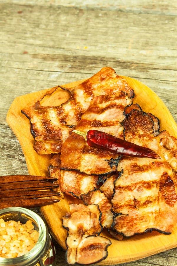 烟肉烤了 在表上的酥脆煮熟的烟肉 不健康的食物 肥胖病的风险 自创的烤肉 库存图片