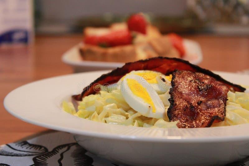 烟肉熟蛋圆白菜沙拉早餐用被烘烤的面包和草莓 库存图片