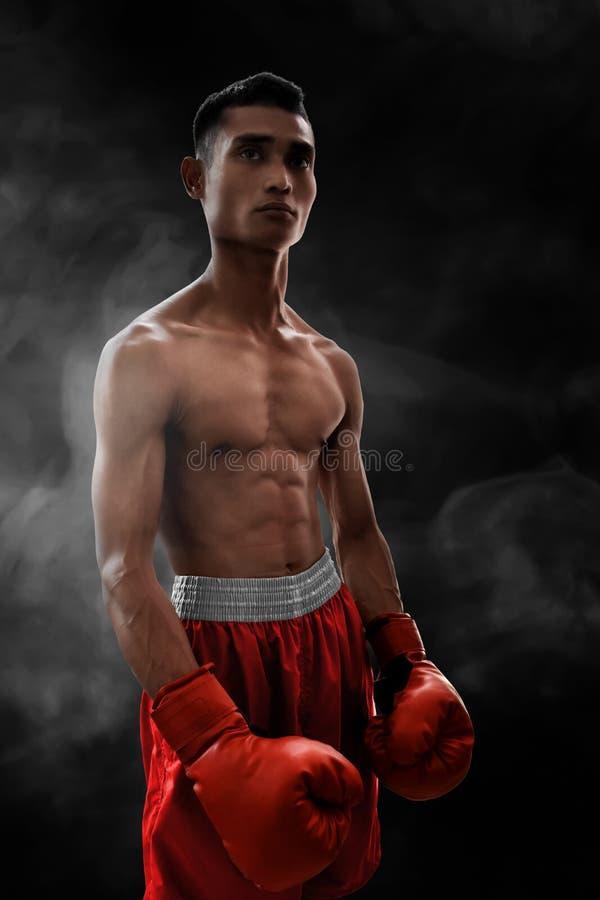 烟背景的坚强的肌肉拳击手 库存图片