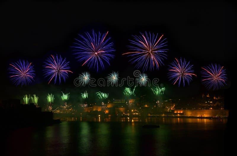 烟花 在黑暗的天空的烟花爆炸与城市sillouthe和五颜六色在水反射在瓦莱塔,马耳他 紫罗兰色的烟花 库存照片