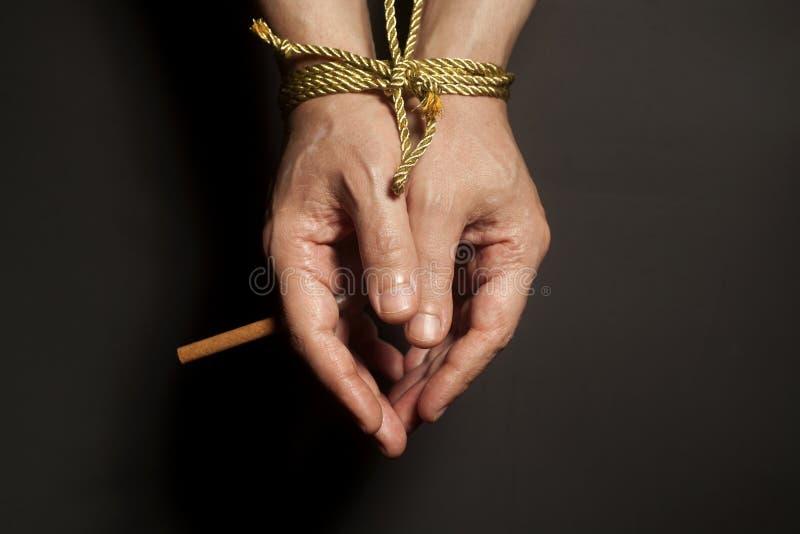 烟草瘾 在男性手上的香烟绑住与绳索 库存图片