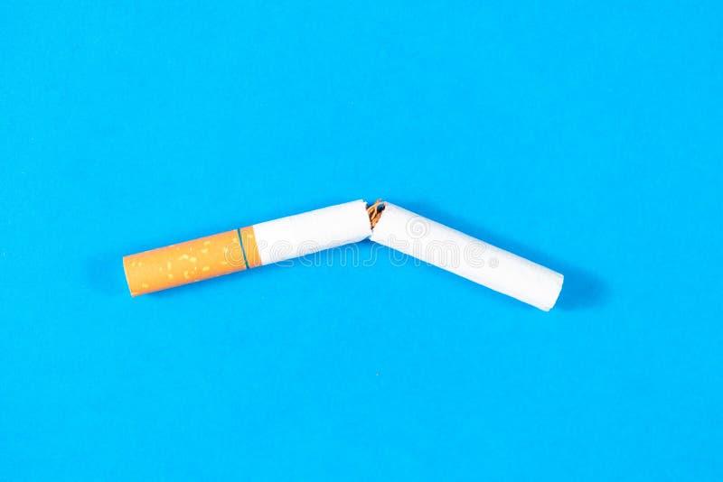烟草香烟打破紧密有蓝色背景 图库摄影