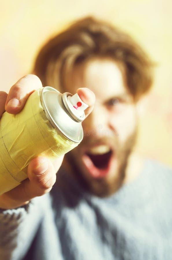 烟雾剂喷射油漆罐头在手中有胡子的恼怒的人 免版税库存图片