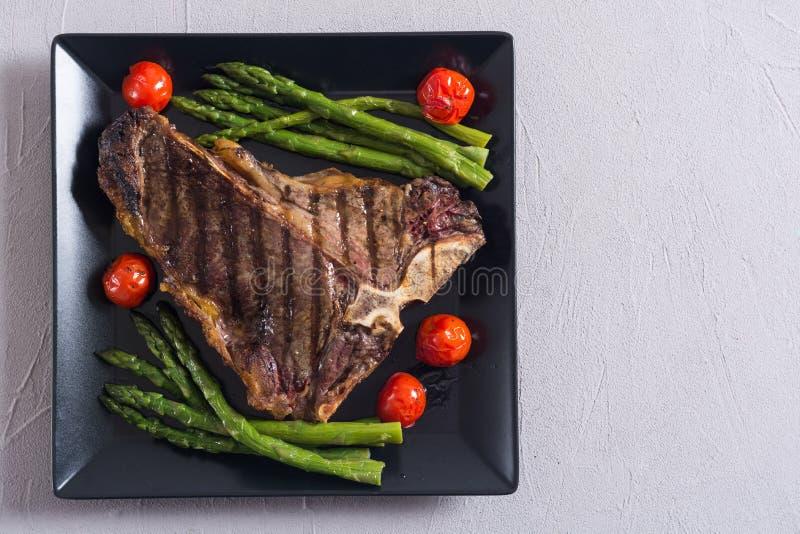 烤丁骨牛排用芦笋和西红柿 库存图片