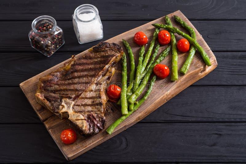 烤丁骨牛排用芦笋和西红柿 免版税库存照片