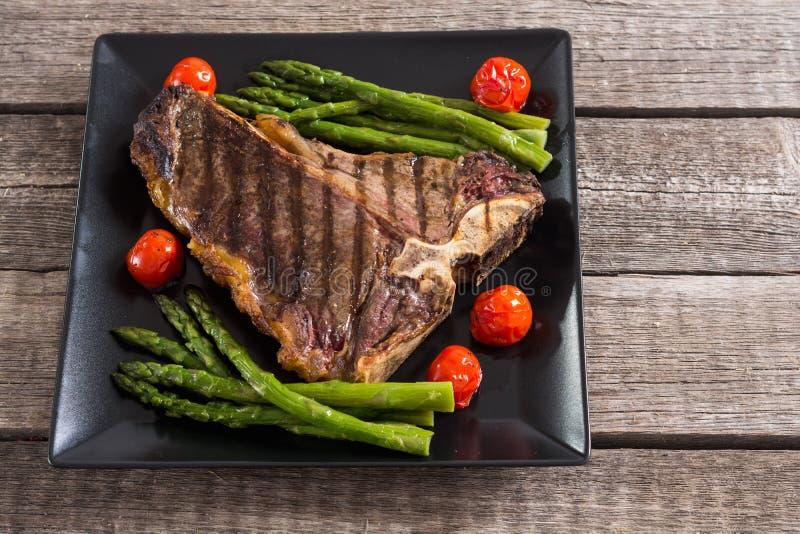 烤丁骨牛排用芦笋和西红柿 免版税库存图片