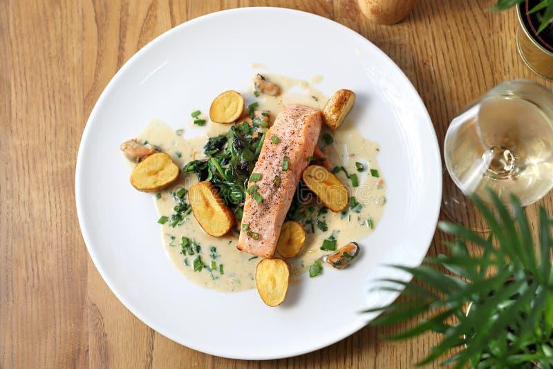 烤三文鱼内圆角用在奶油沙司的被烘烤的土豆用香葱 库存照片