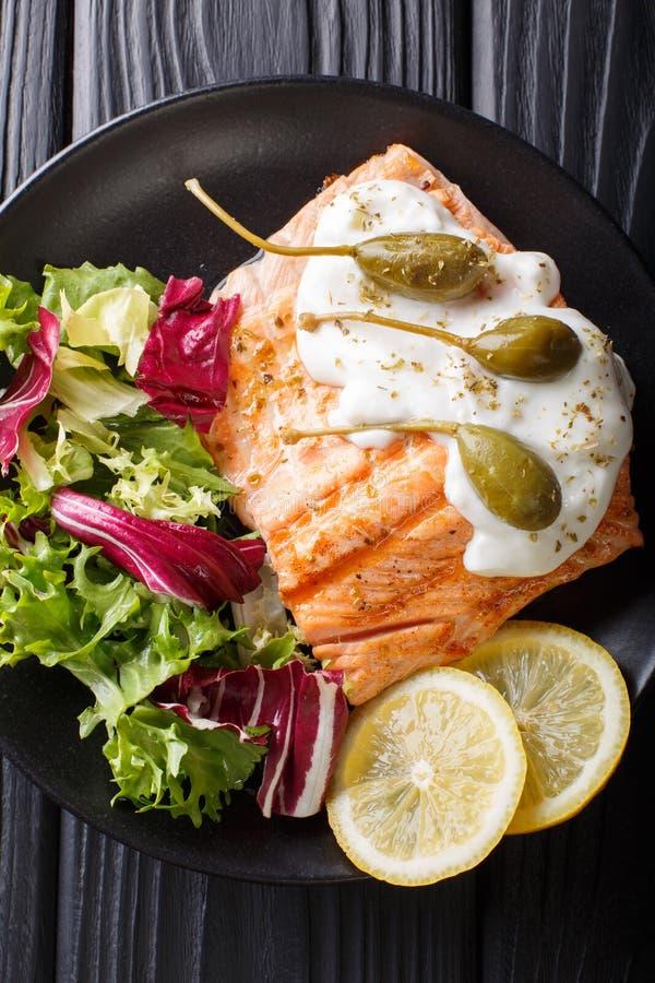 烤三文鱼内圆角用奶油沙司、雀跃,柠檬和新鲜 库存图片