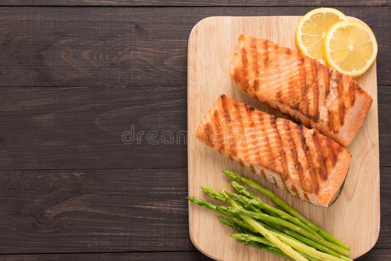 烤三文鱼和柠檬,在木背景的芦笋 免版税库存照片