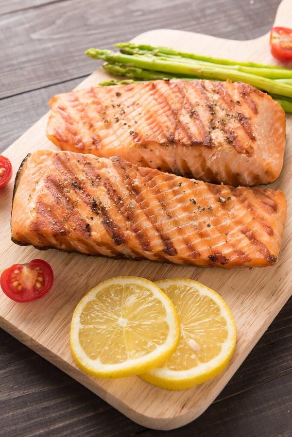 烤三文鱼和柠檬,芦笋,在木backgr的蕃茄 库存图片