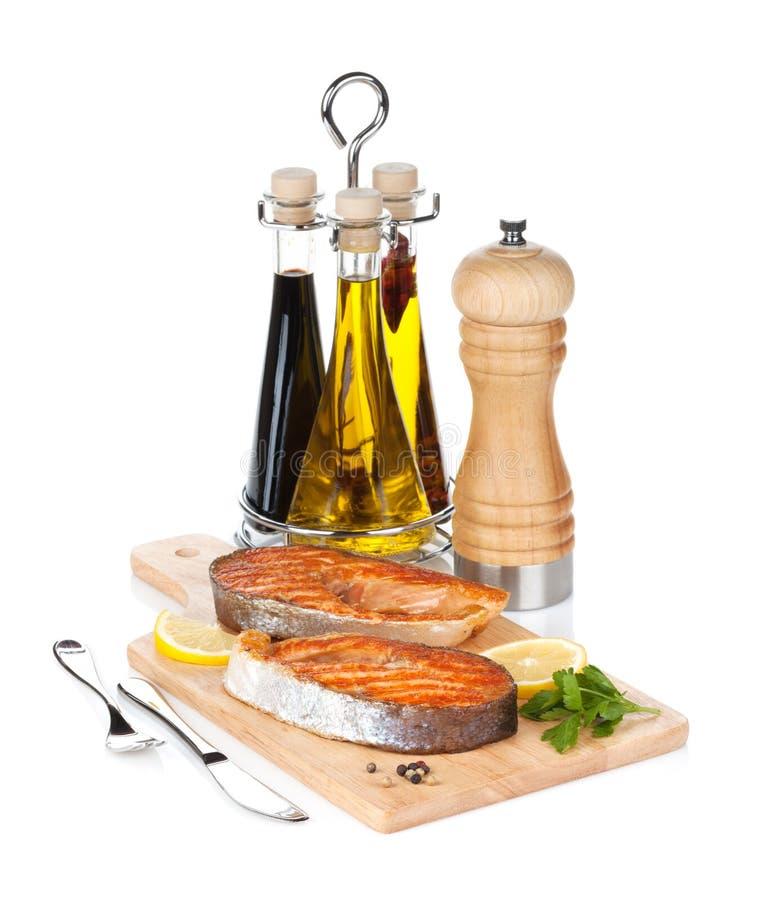 烤三文鱼用在切板的柠檬和草本 库存照片
