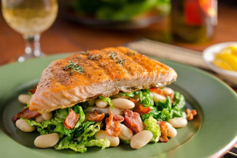 烤三文鱼用无头甘蓝、白豆和烟肉 库存图片