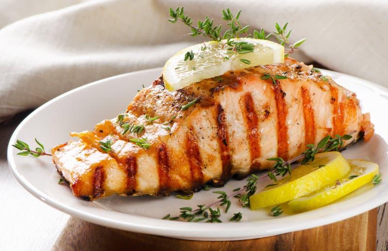 烤三文鱼用柠檬、橄榄和新鲜的麝香草 库存照片