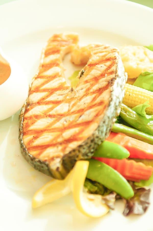 烤三文鱼用柠檬和沙拉在白色板材,被弄脏的绿色背景 明亮的阳光 r 库存图片