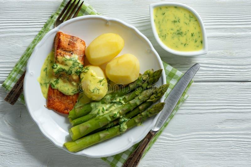 烤三文鱼用煮沸的土豆和芦笋在乳脂状的莳萝调味汁 免版税库存照片