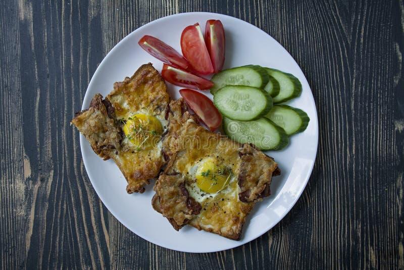 烤三明治用鸡蛋、菜和烟肉在黑暗的木背景 鲜美早餐 库存图片