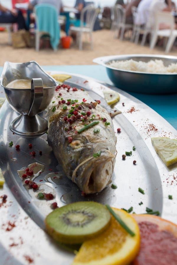 烤与柠檬切片和荷兰芹的煮熟的鱼 免版税库存图片
